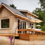 modern small rustic cabin design with front porch and umbrella patio and glass window accent
