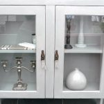 modern storage cabinet with glass doors presented in white scheme with chandeliers and ceramics inside