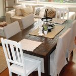 modern white dining space with ikea chair design and rust8ic wooden table and wooden floor and white sofa and creamy rug