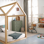 nice-toddler-floor-bed-with-house-frame-surrounded-with-white-wall-and-some-toys-on-the-floor-and-floating-shelf-also-chair-near-window-and-grey-curtain