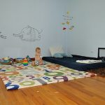 nice-toddler-floor-bed-with-montessori-method-and-the-dark-blue-bed-with-white-pillow-on-the-wooden-floor-also-mirror-and-rocking-chair