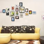 Nice Wall Decoration With Framed Photos Hang On The Wahite Wall In Living Room With Yellow Sofa And Brown Cushions And Pretty Standard Lamp