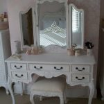 old-hollywood-style-vanity-table-and-makeup-vanity-table-and-white-dresser-near-white-flower-wallpaper-also-cosmetics-and-mirror-reflects-white-bed