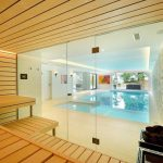 perfect bathroom with sauna design with open concept and double wooden bench overlooking pool