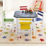 playful kids room idea with black white small art table for kids with yellow and red chairs and stars patterned area rug