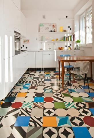 playful mosaic mexican kitchen tile flooring idea with white cabietry and wooden dining table and wire chairs and window