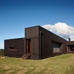 posh black wooden rustic home beach design with boxy shape and open concept on grassy meadow