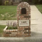 rustic brick mailbox design idea with arched style and planter box in cross road with grassy meadow