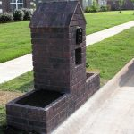 rustic gray brick mail box design like home with box planter on the yard aside road with grassy meadow
