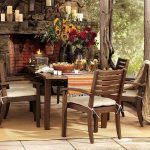rustic outdoor garden living space with fireplace with rustic cheddar and table and wooden cairs on creamy area rug