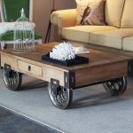 rustic-wood-coffee-table-with-wheels-on-grey-carpet-on-dark-grey-floor-and-green-chair-and-sofa-and-owl-pillow-and-standard-lamp