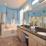 sea-themed-bathroom-with-white-sink-and-beige-cabinet-and-net-on-the-blue-wall-and-flowers