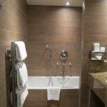 seren bathroom idea with small bathtub and wall mirror and towel target idea beneath brown tile wall design