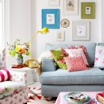 shabby chic spring mood interior with gray sofa and colorful chair and cushions and pink coffee table and patterned area rug