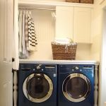 simple and small laundry room with navy blue washing machine and basket shelves and chandelier