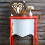 small and cute coral color console table with diamond patterned decoraton and white flower beneath rustic metal siding