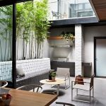 small courtyard idea with seatings and round table and concrete patio and planter boxes and wooden kitchen bar