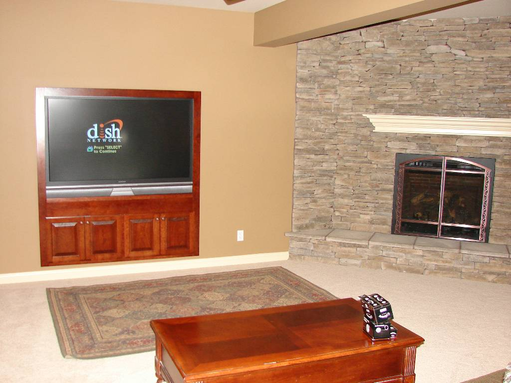small in wall entertainment center in living room ideas with small rug area and wooden coffee table plus stunning fireplace and natural stone wall
