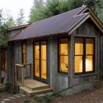 small rustic cabin idea with open plan and glass window and door and stairs and caramel tone roof
