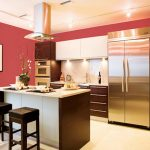 soft pink good color to paint a kitchen idea with pink wall paint and white brown cabinetry and stainless steel refrigerator and small island and brown leather stools