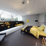 spacious bedroom decor with gray and yellow color combination with gray sofa and black shelves and open plan