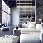 spacious interior design with loft idea with open concept and tall brick wall and white luxurious sofa and telescope and perfect partition