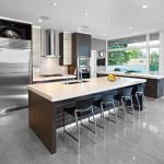spacious modern kitchen design with wall storage and white black island bar table and black stools and floor to ceiling glass window and laminated flooring