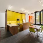 spacious modern kitchen studio with open concept and yellow wall accent and small breakfast nook with green chairs and wooden floor and island