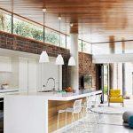 spacious modern vintage loft kitchen idea wih skylight and wooden ceiling and marble flooring and yellow chair and white stools