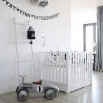 spacious nursery design idea with white siding with white crib and ladder and wall decoration and laminated bamboo flooring