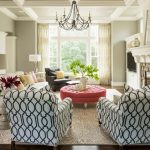 spring mood interior design with black and white chairs and red coffee table on creamy area rug beneath chandelier