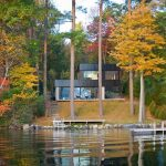 structural forest house design with two storey overlooking lake with deck and fall tree tone