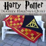 stunning hogwart school logo on harry potter throw blanket of red and yellow and black plaid pattern on wooden bench on  paved patio