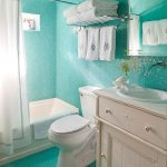 stunning turquoise blue bathroom with towel shelf and vanity and tub and curtain and toilet seat and fresh flooring