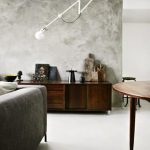 stunning vintage interior with ombre gray wall texture and old wooden console table and round table and gray sofa ide aand unique lamp