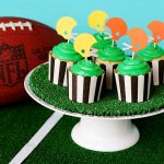 super bowl party decoration idea with some colorful cupcakes on gren plate with ball on field
