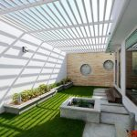super modern courtyard design with white concrete fence and transparent canopy and green grassy meadow and planter boxes and seating