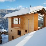 super stylish modern home on hillside idea with beige wooden tone and glass window on snowy hill with mountain view