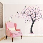 temporary wall covering idea with cherry blossom theme and pink sofa in living room with brown draped window