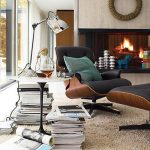 the-most-comfortable-black-Eames-Lounge-chair-on-the-beige-carpet-near-books-and-a-steel-table-lamp-on-the-glass-table-and-large-glass-window-also-a-fireplace