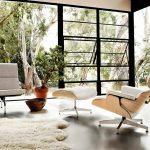 the-most-comfortable-white-Eames-Lounge-chair-near-white-fluffy-carpet-and-white-chair-and-black-cushion-also-open-door-and-glass-windows-with-beautiful-nature-outside-
