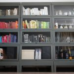 Three Coloumns And 4 Rows With 12 Doors Metal Barrister Bookcase For Books Novels Speaker System Bottles Glasses And Wooden Floor