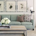 transitional-family-room-with-soft-tosca-sofa-and-pillows-and-rustic-table-and-white-flowers-centerpiece-and-books-and-carpet-and-pictures-on-the-wahite-wall