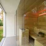 tropica bathroom idea with open plan and large sauna with bench and table and glass siding and green view outside