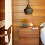 tropical-bedroom-with-wooden-floating-nightstand-with-two-drawers-hang-on-the-wooden-wall-and-candlelight-and-books-and-red-flowers-with-black-hanging-lamp