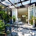 tropical courtyard ides with canopy and gray chairs and metal table with rustic stone patio and glass door