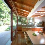 tropical modern kitchen studio design with sliding glass door with breakfast table with creamy chairs beneath wooden ceiling with lush vegetation