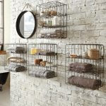 vintage black wire towel shelves idea with cage style and round framed wall mirror on rustic brick siding