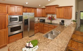 vintage kitchen design idea with wooden cabinetry and long island with wooden stools and river gold granite countertop