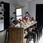 vintage ruustic wooden dining table idea with black stools and pendant and wall racks and centerpiece